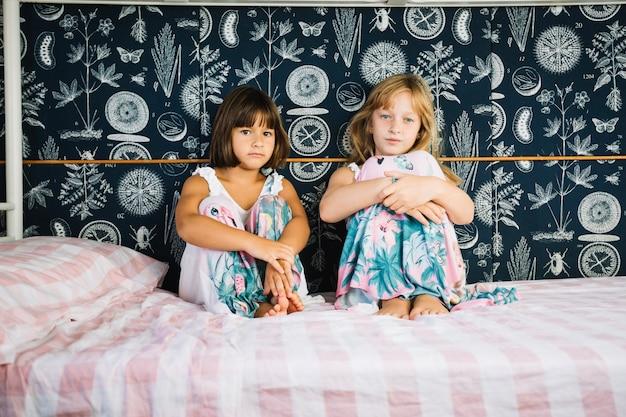 Девушки сидят на кровати