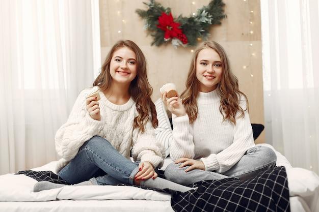 침대에 앉아있는 여자. 컵 케이크와 여성. 크리스마스를 준비하는 친구.