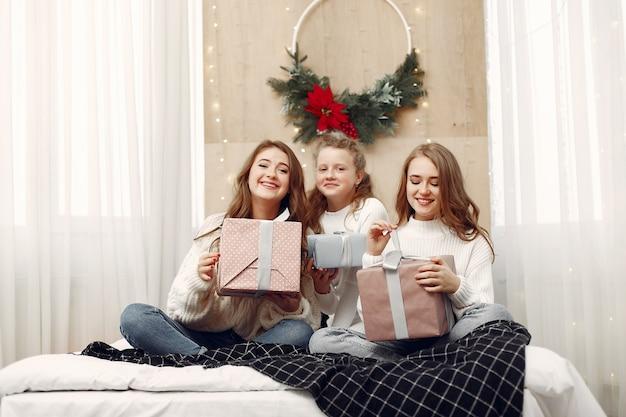 ベッドに座っている女の子。ギフトボックスを持つ女性。クリスマスの準備をしている友達。