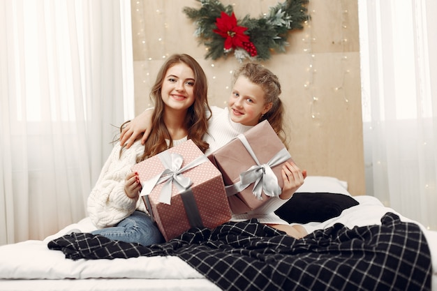 ベッドに座っている女の子。贈り物を持っている女性。美しさはクリスマスの準備をしています