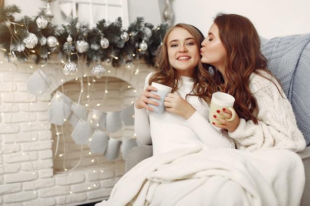 椅子に座っている女の子。カップを持つ女性。クリスマスの準備をしている姉妹