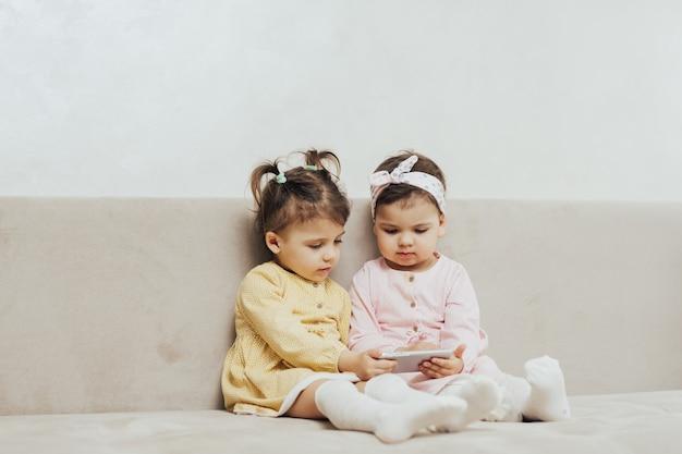 Девушки сидят на диване и смотрят мультики