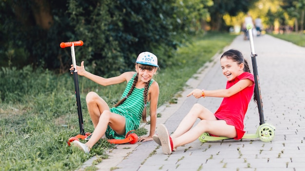 Girls sitting on their push scooter making fun in the park