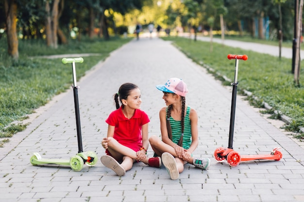 Girls sitting on walkway with their push scooters on walkway in the park