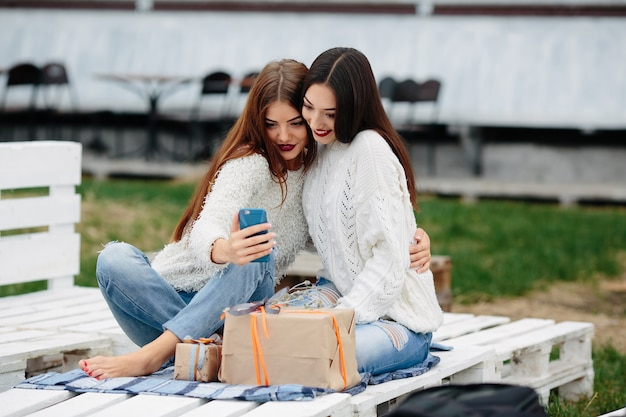 Girls sitting on a white wooden pallet with a gift looking at a mobile