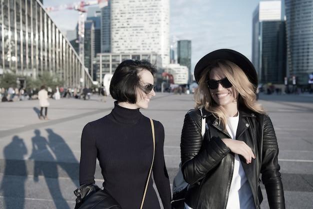 파리 라데팡스 비즈니스 지구에서 소녀들이 세련된 옷을 입고 미소를 짓고 있다. 행복한 여성이나 소녀들은 화창한 날 도시 환경에서 걷습니다. 휴가, 여행, 방랑벽. 패션, 뷰티, 봐.
