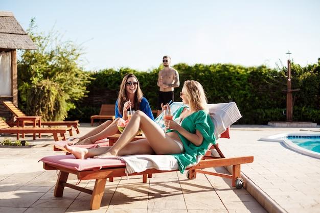 Ragazze che sorridono, bevendo cocktail, prendendo il sole, sdraiati vicino alla piscina