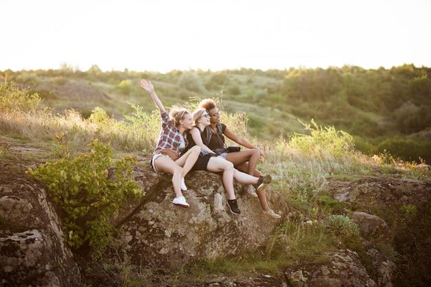 Девушки улыбаются, сидя на скале, наслаждаясь видом в каньоне