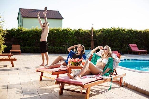 Girls smiling, sunbathing, lying on chaises near swimming pool