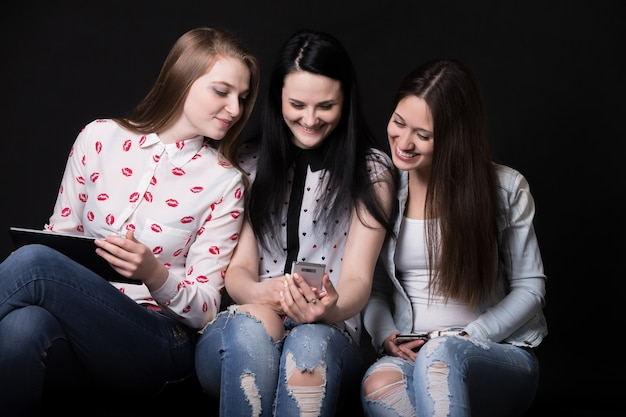 Girls smiling whilen looking at a mobile