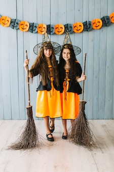 Girls in sorceress clothes hugging and holding broomsticks
