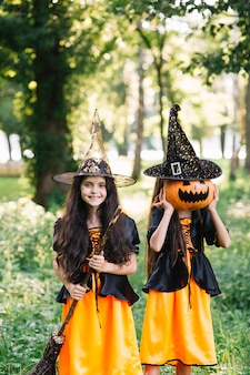 Girls in sorceress costumes holding broomstick and closing face by pumpkin