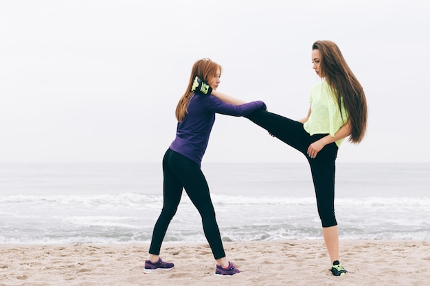 Girls in sportswear are stretched on the beach