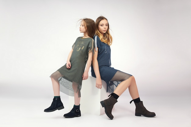 Girls in spring boot shoes posing on a white background