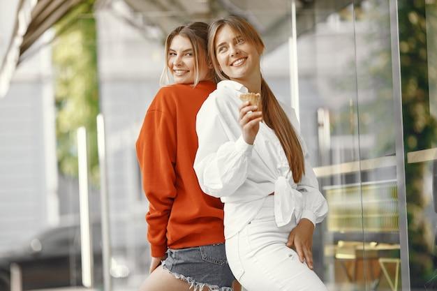 Девушки стоят в летнем городе с мороженым
