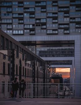 Девушки, стоящие возле перил, наблюдая закат