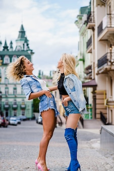 Girls standing outside laughing posing