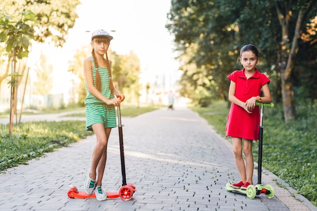 Girls standing with scooter on pavement
