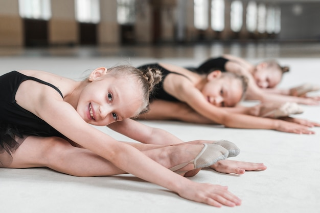 Girls stretching forward with her friends before dancing in studio