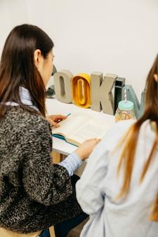 책을 읽고 테이블에서 공부하는 여자