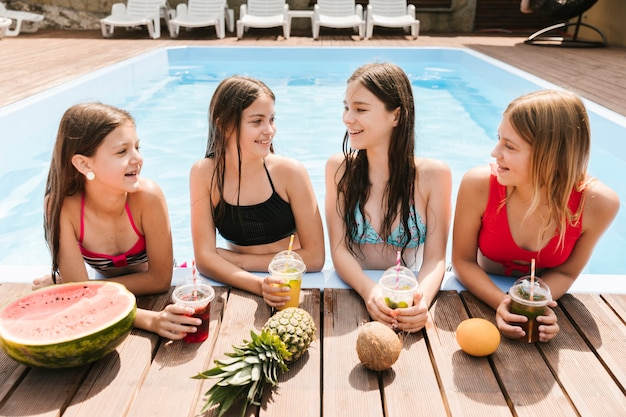 Girls surrounded by fruit in swimming pool