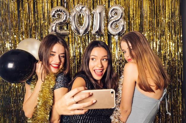 Ragazze che prendono selfie sulla notte di nuova anno