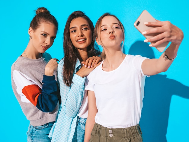 Girls taking selfie self portrait photos on smartphone.models posing near blue wall in studio.female making duck face on frontal camera