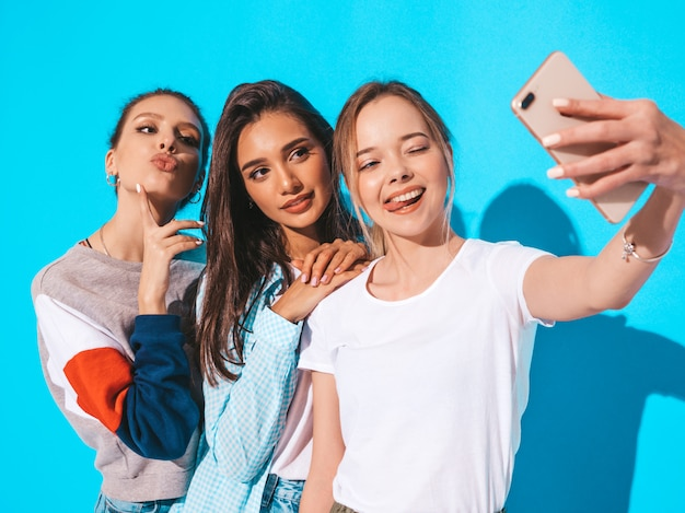Girls taking selfie self portrait photos on smartphone.models posing near blue wall in studio.female showing positive emotions