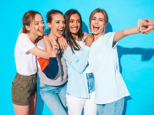 Girls taking selfie self portrait photos on smartphone.models posing near blue wall in studio,female showing positive face emotions