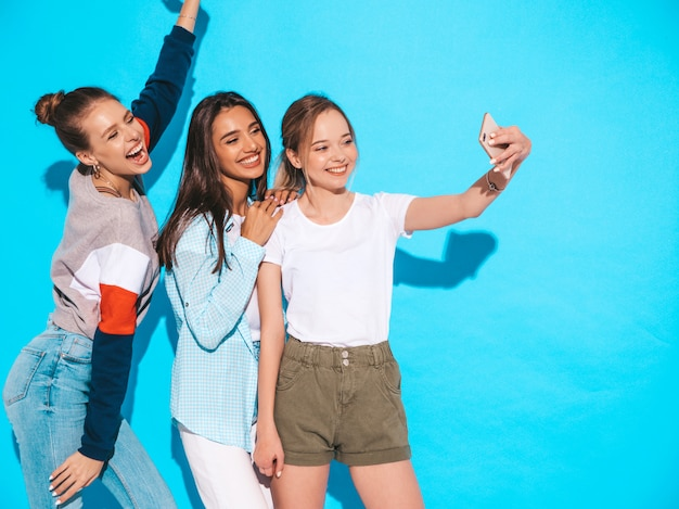 Girls taking selfie self portrait photos on smartphone.models posing near blue wall in studio.