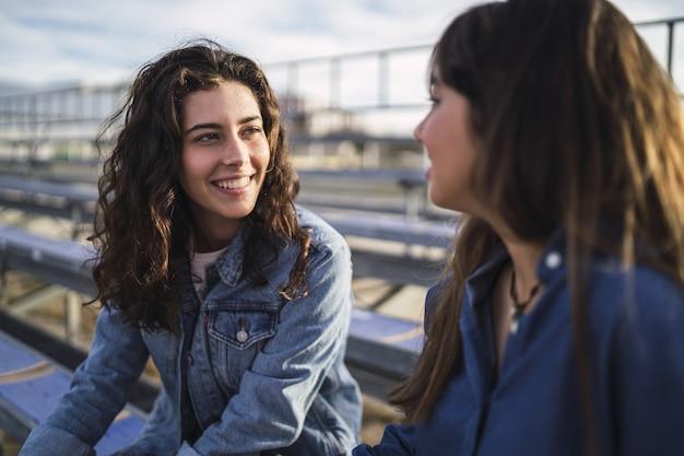 Девушки разговаривают друг с другом в парке днем