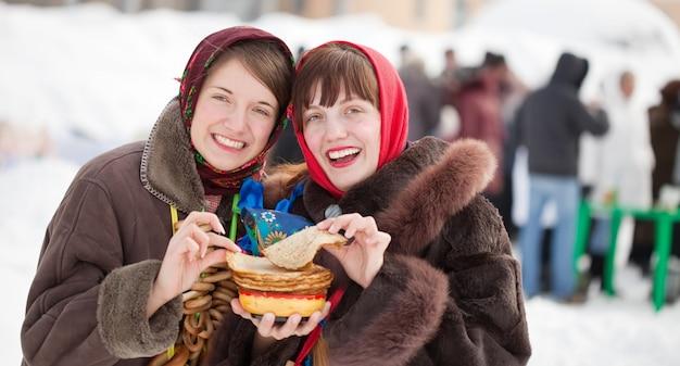 Shrovetide 동안 팬케이크를 시음하는 여자