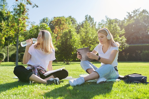 バックパック、本、デジタルタブレット、水のボトルを飲むと公園の緑の芝生に座っている女の子の10代の学生。大学、大学、学校、教育と知識、思春期のライフスタイル