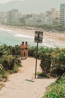 Girls in their bikini standing and looking to the beach in rio de janeiro