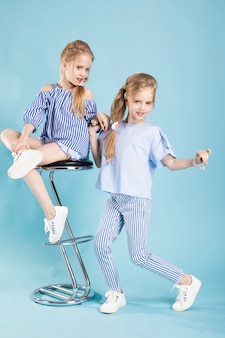 Girls twins in light blue clothes are posing near a bar stool on a blue .