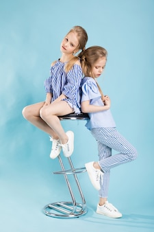 Girls twins in light blue clothes are posing near a bar stool on blue