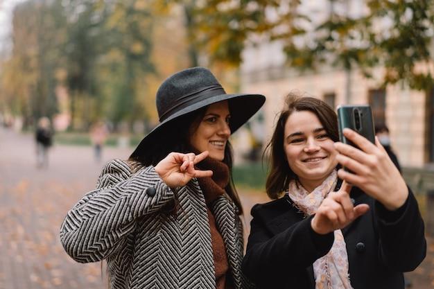 Девушки используют телефон для видеозвонка друзьям в парке