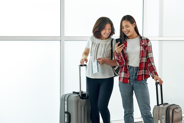 Girls using smartphone checking flight or online check-in at airport, with luggage.