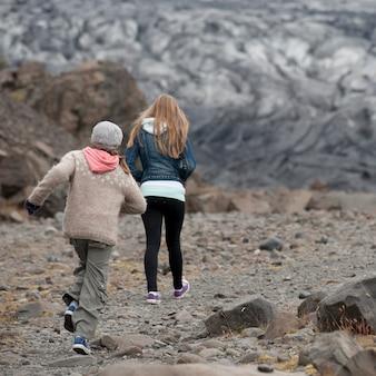Girls walking away on glacial debris