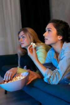 Девушки вместе смотрят netflix в помещении