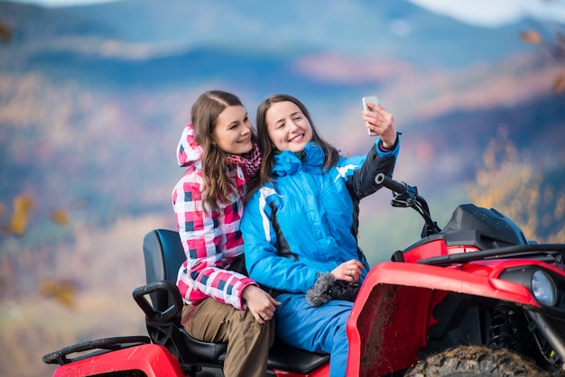 Girls in winter jackets on red atv