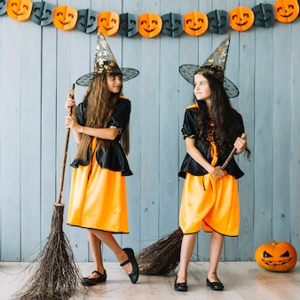 Girls in witch costumes holding broomsticks