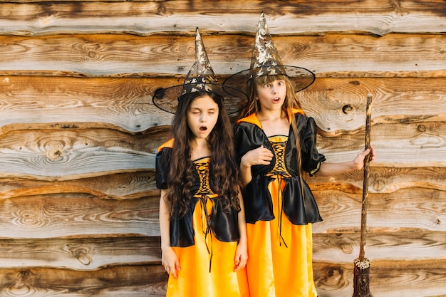 Girls in witch costumes making faces on wood background