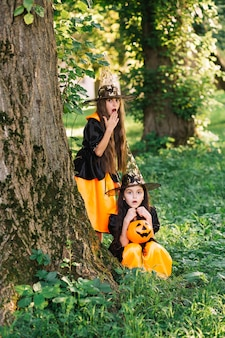 Girls in witch costumes showing surprise near tree