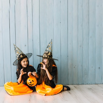 Girls in witch costumes sitting on floor doing scary gestures