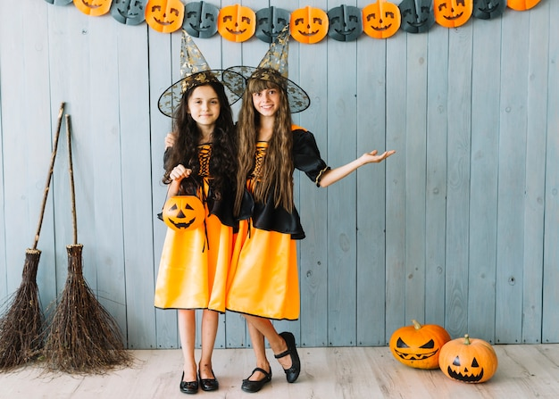 Girls in witch dresses embracing in room with pumpkins and brooms