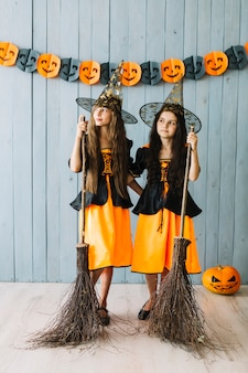 Girls in witch suits hugging and holding broomsticks