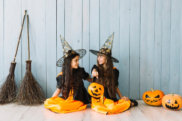 Girls in witch suits and pointy hats holding halloween basket sitting on floor