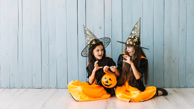Girls in witch suits sitting on floor doing frightening gestures