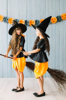 Girls in witch suits taking broomsticks between legs